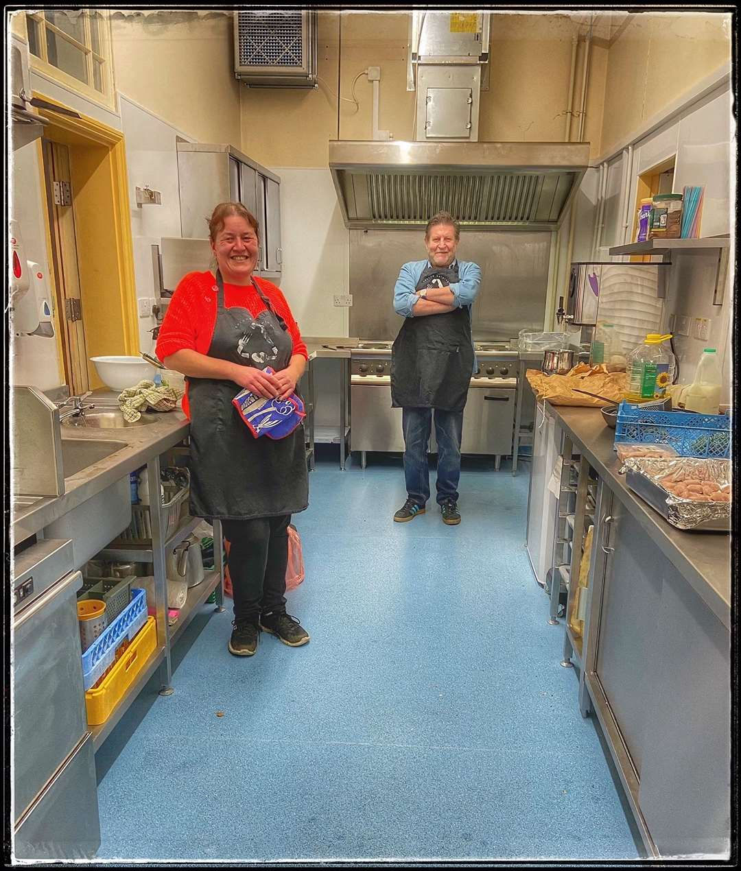 Volunteer cooks Julie White and Paul Dunn cooking takeaway meals in the newly renovated kitchen
