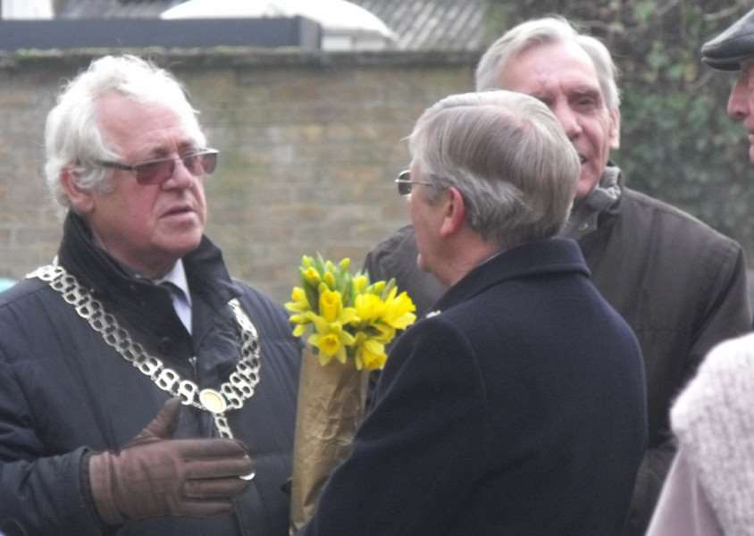 The Mayor of Stamford John Dawson holds the daffodils he laid during the service while he chats to other councillors
