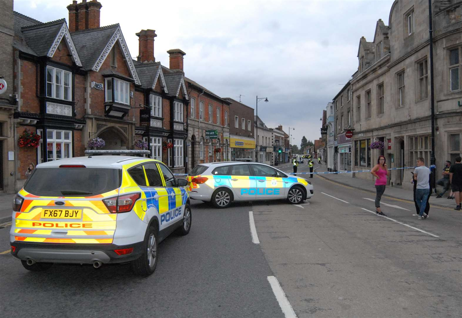 Bourne street closed off by police after man climbs on roof of business
