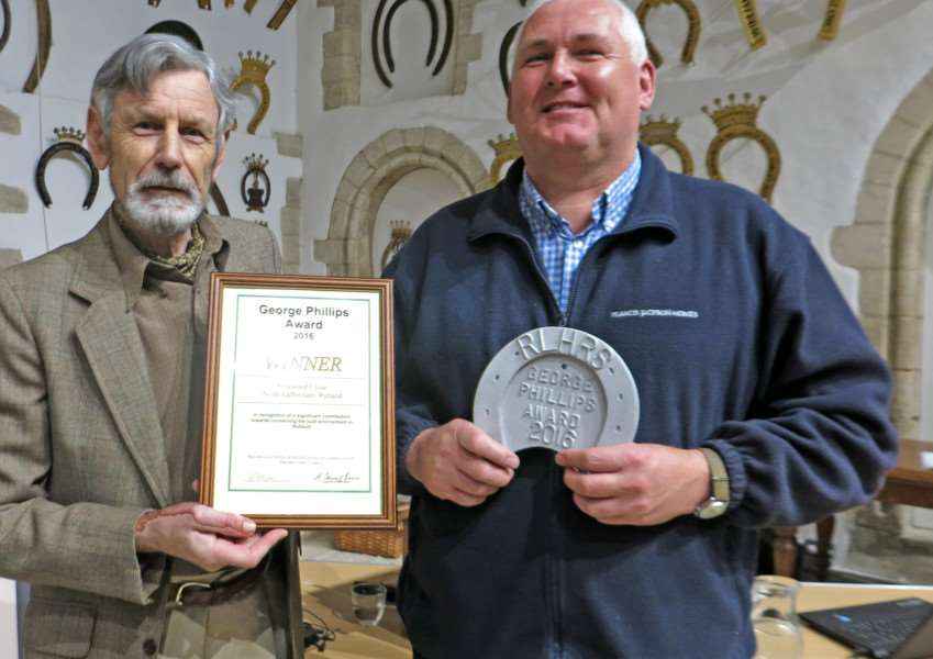 Graham Sloan receives the George Phillips Built Environment Award plaque and certificate from Tim Clough for Rosewood Close, North Luffenham