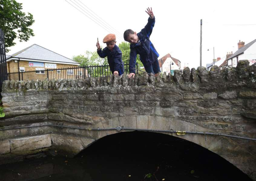 Freddie and Archie Lound playing Pooh sticks at Bourne bridge EMN-150826-171230009