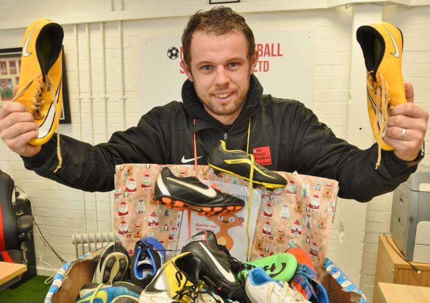 Glenn Vaughan of One Touch Football Soccer School with football boots for disavantaged children EMN-160512-150257009