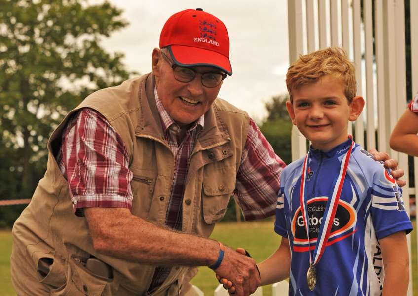 OMNIUM KID: Jack Bowser is congratulated by 1960s Tour de France rider Vin Denson at the Mildenhall Cycling Festival. Photo by Tim Bryett.