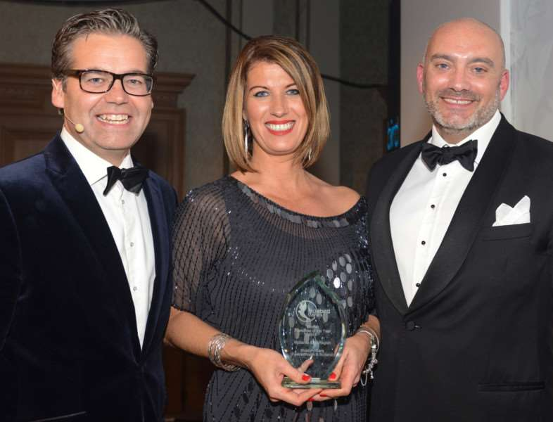 Leisa MacKenzie and Tim Carey receive the award from Duncan Berry, chief operative officer of Bluebird Care, left.
