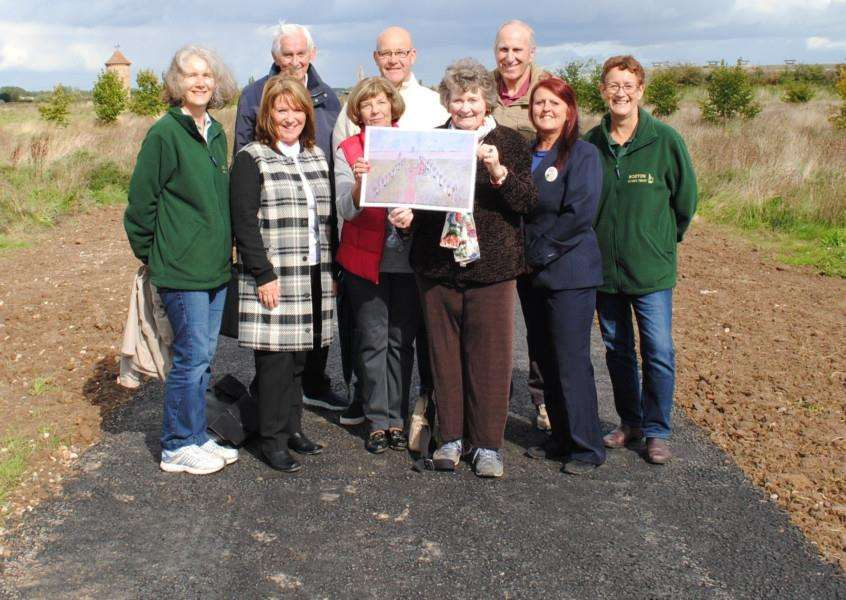 Anne Bourne and supporters hold plans for the Lincolnshire Road Victims Memorial at Westgate Woods in Wyberton. Photo supplied by Boston Borough Council.
