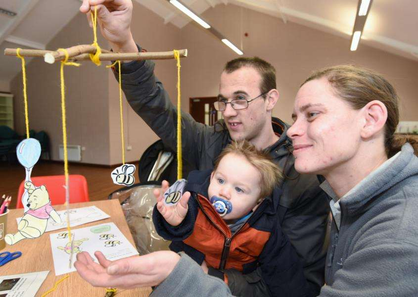 Visitor experience assistant Sarah-Jane Bancroft helps Graham Tecklenberg and his son Lewis, 1, make a mobile