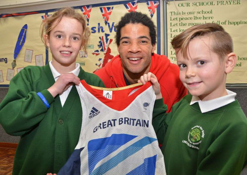 Paralympian athlete Sam Ruddock shows young ambassadors Katie Marsh and Kyle Roberts his London 2012 competition vest at Linchfield Community Primary School, Deeping St James. Photo by Tim Wilson.
