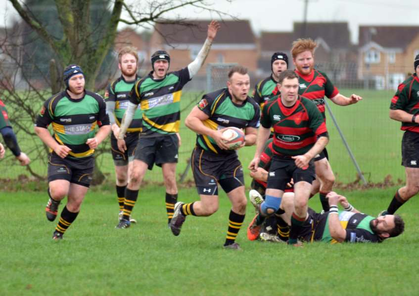 Lance Charity (carrying the ball) who scored two tries for Deepings in their 29-22 win over rivals Thorney. Photo by Tim Wilson.