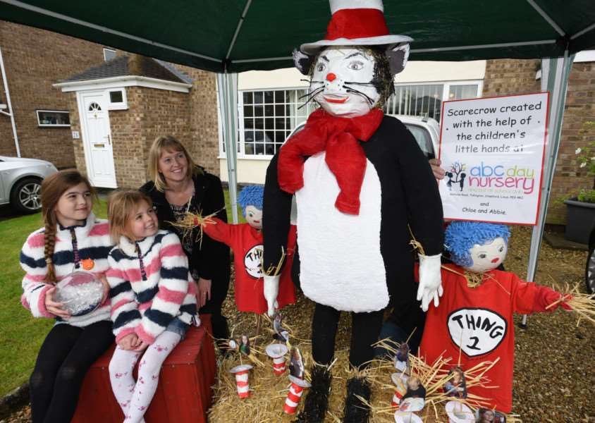 Uffington scarecrow festival - Wendy Graham and daughters Chloe (11) and Abbie (5) with the ABC Nursery scarecrow EMN-150305-192804009