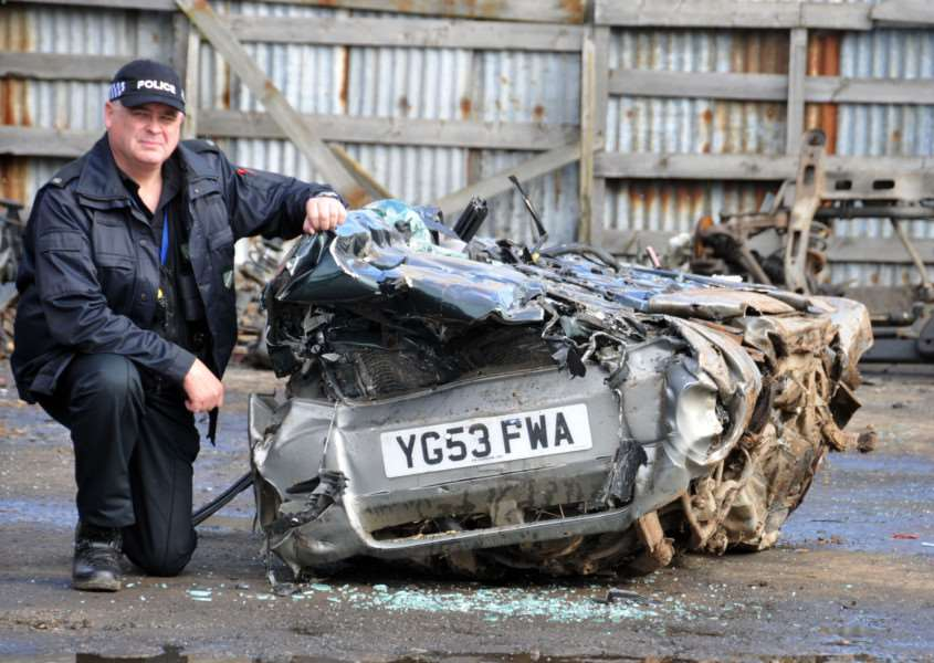 COUNTRYSIDE LAW: PC Nick Willey next to a crushed Subaru Forrester which was seized by police in connection with harecoursing on farmland in Sutton St James in November 2013. Photo: (TIM WILSON): SG151014-139TW.