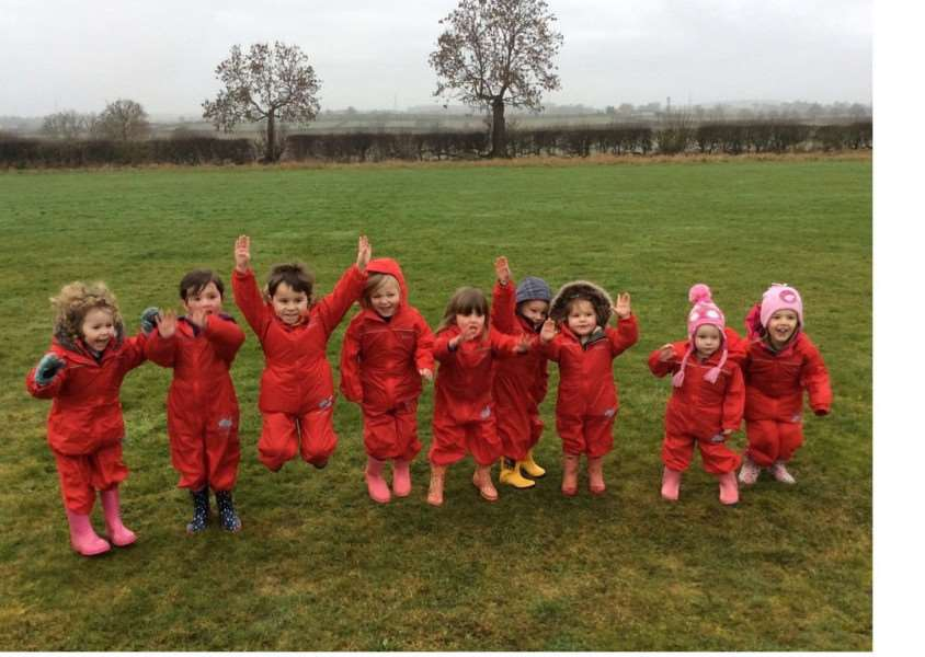 Happy faces at Corby Glen Playgroup in their new waterproof jumpsuits.