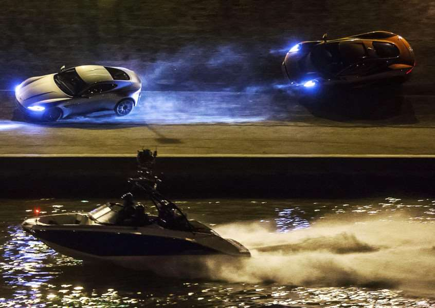 A Scarab jet boat provided by 158 Performance in Tallington films a Jaguar as it runs after an Aston Martin along the Tiber River banks during the shooting of the James Bond movie Spectre in Rome.. Photo: AP/Angelo Carconi, Ansa EMN-150411-102111001