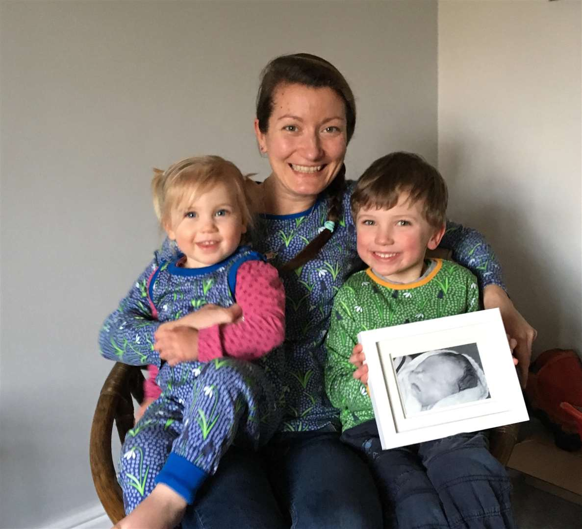 Frankie with Ayla and Jago holding a photo of Esme