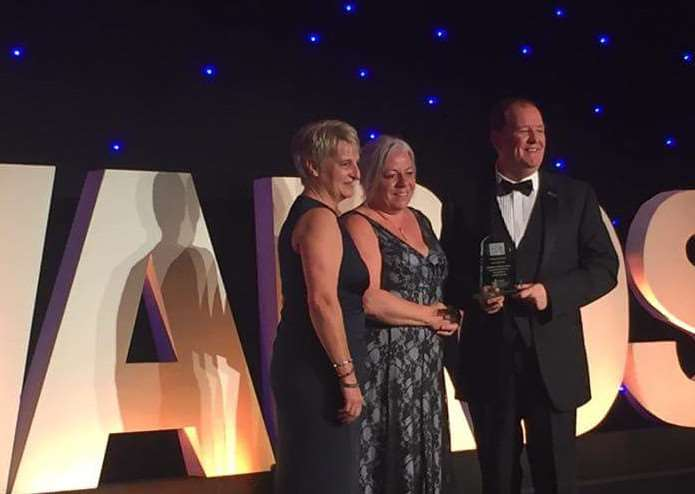 L-R Mary Spier, Steve Pratten and Mandy Lowe from the Community Response Team on stage receiving their award.