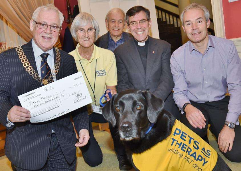 Mayor of Stamford John Dawson with Pets as Therapy volunteer Rosemary Wooler and Jessie the labrador receiving a cheque from Stamford Dog Show with Roger Ing, Rev Andy Fyall and Conan Lewis from the show. EMN-161118-151147009