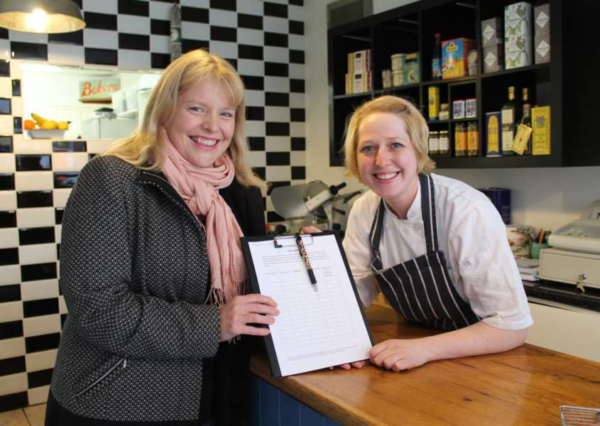 County Councillor Sarah Dodds (Lab, Louth North) hands over a petition to Roxy Warrick at Royston's Deli in Queen Street, Louth.