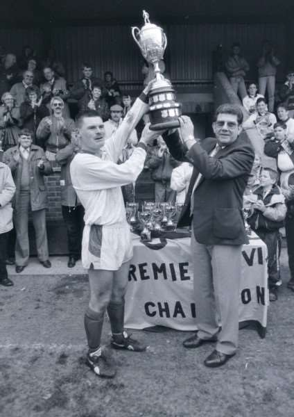 Wakes skipper 'Steve Appleby accepts the UCL Premier Division trophy from league chairman and ex-Bourne Town manager Terry Bates at the Abbey Lawn.