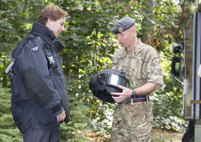 Sgt Miles Truscott shows the bomb disposal suit to reporter Alex Moore.