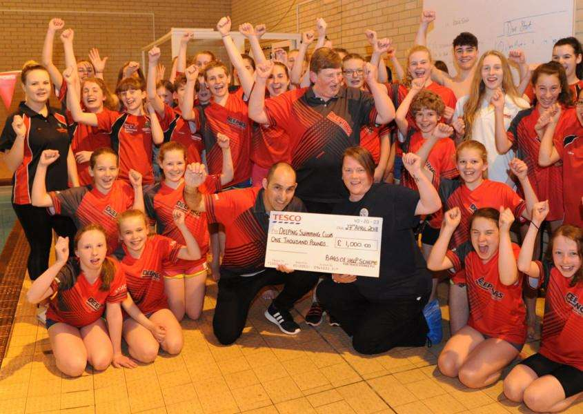 Tesco community champion Michelle Bateman presents the cheque to'Deepings vice chairman Steve Tappern with head coach Lynn Chapman and club swimmers looking on. Submitted.