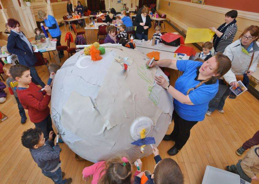 Stamford Arts centre family fun day. Children and staff drawing on a giant planet EMN-160219-174811009