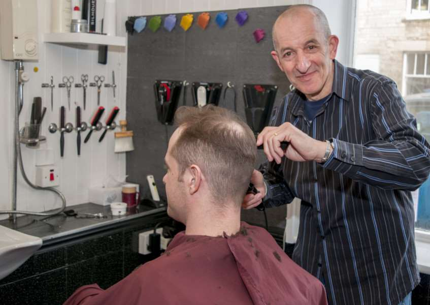 Mimmo Florio cuts customer Sam Richardson's hair on his last day at work