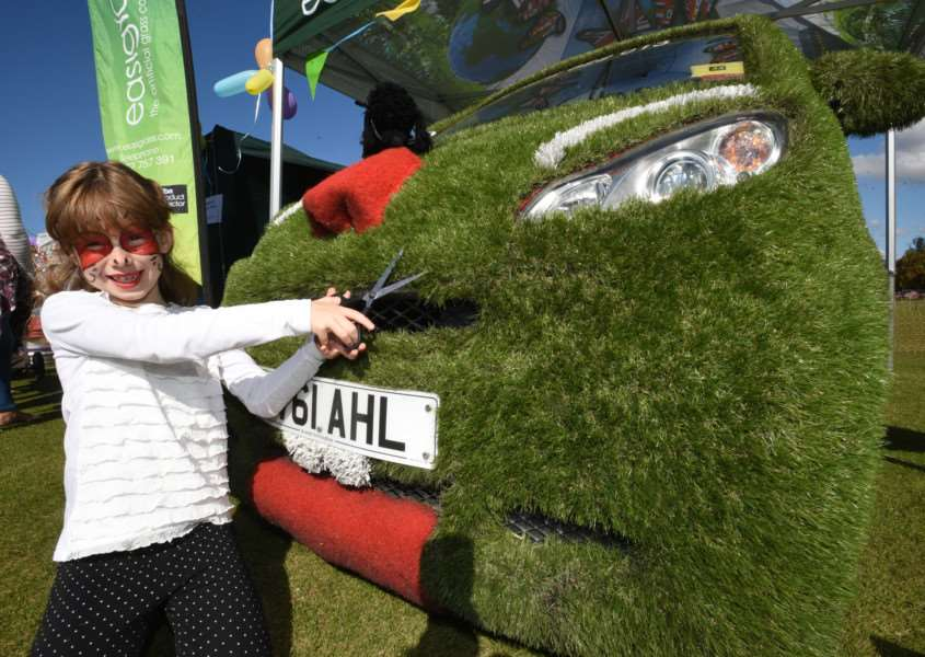 Ketton village fete. Sophie Waycot (7) with the Easygrass Car covered in synthetic grass EMN-150927-170412009