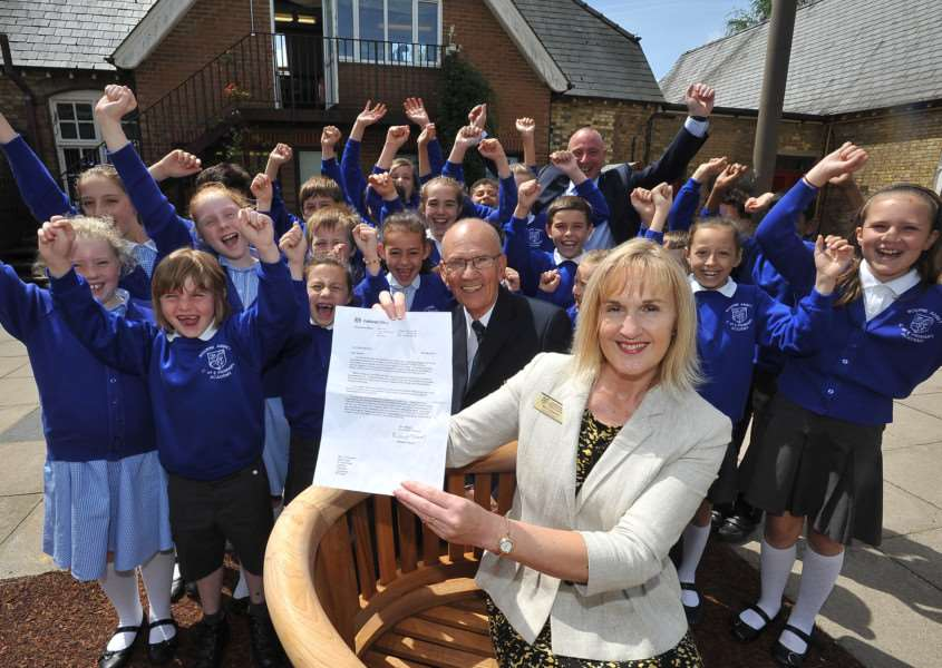 Cherry Edwards with pupils, chairrman of governors John Kirkman and vice chairman Duncan Pickering (back) celebrating notification of the OBE award. Photo by David Lowndes.