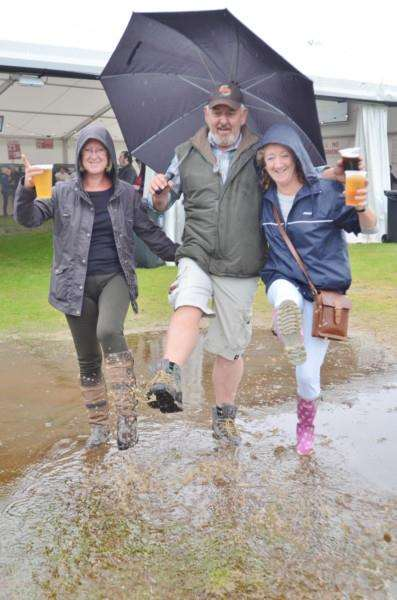 Helen Mason, Kevin Winterton and Diane Warburton wade through a flooded area outside the beer tent