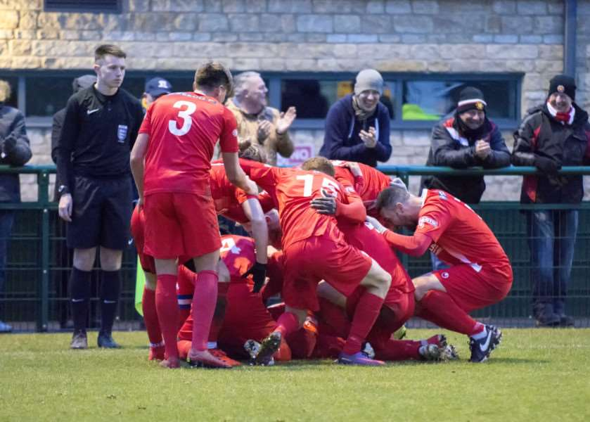 Ben George is buried by delighted Stamford players after scoring the second goal in their 3-1 win over Basford. Photo: LEE HELLWING