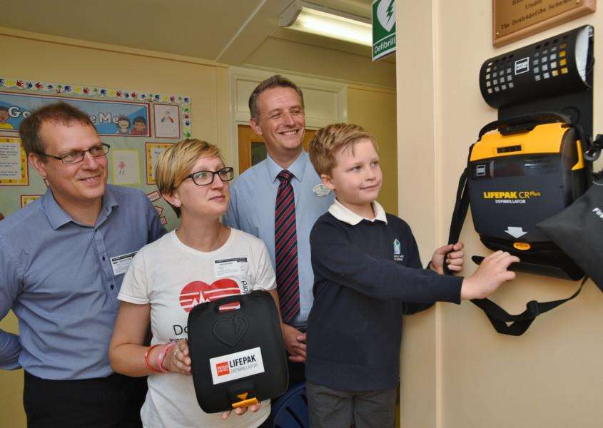 Stewart Jones (Hanson Cement) and Dannii Vincent (Dosh4Defibs) with St Giilbert's C of E primary academy assistant head teacher Richard Westley and pupil Oliver Stanley with the new defib machine at school. EMN-150622-233840009