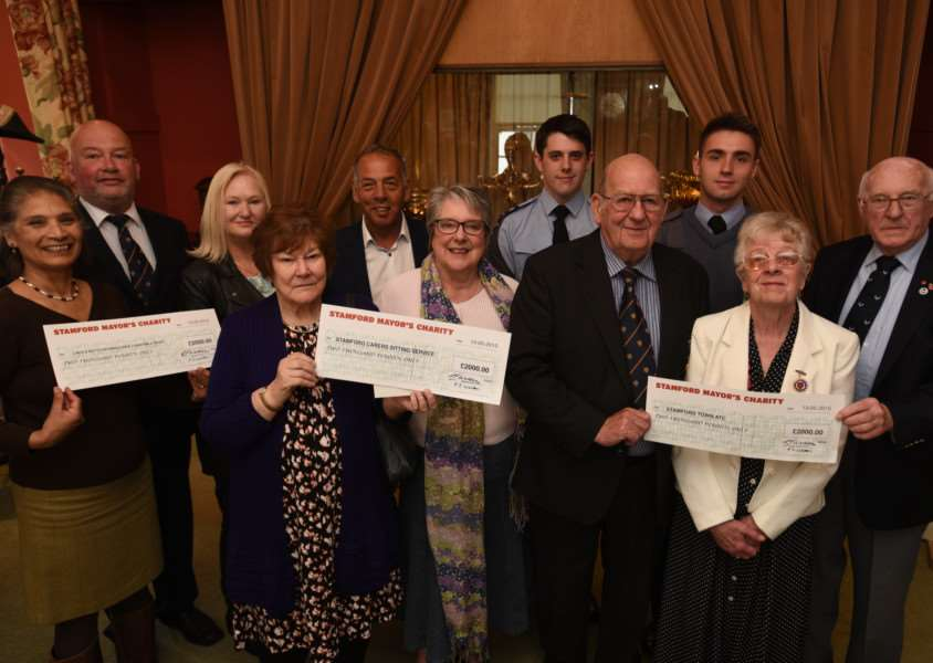 Clem and Pam Walden with town council staff present cheques to representatives from Lincs and Notts air ambulance, Stamford carers and 2071 Air Cadets EMN-150906-152832009