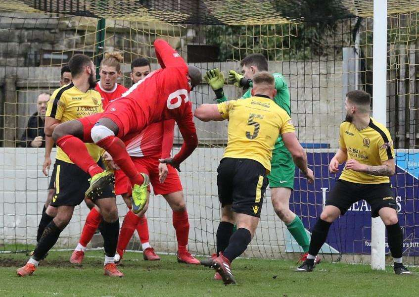 Henry Eze flings himself goalwards as Belper survive another Stamford attack. Photo: Geoff Atton