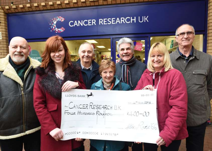 Phil Cox, Cancer Research store manager Naomi Caddell, Dave parry, Sue Cox, Peter and sandee Lane and graham Seal all from Route 66 band handing over a cheque at the Bourne shop of Cancer Research EMN-160502-115322009