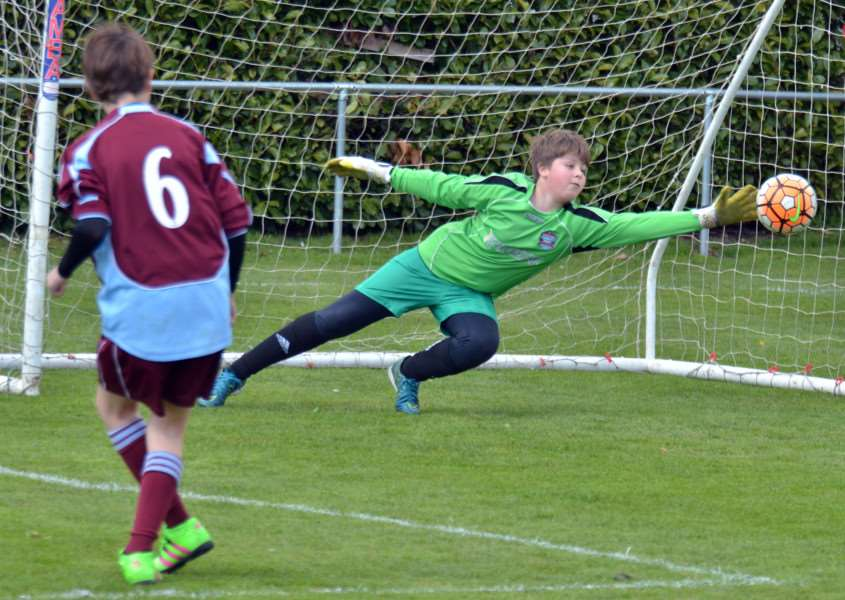 Bourne Town's junior goalkeeper pulls off a penalty save at full stretch. Photo by Tim Wilson.