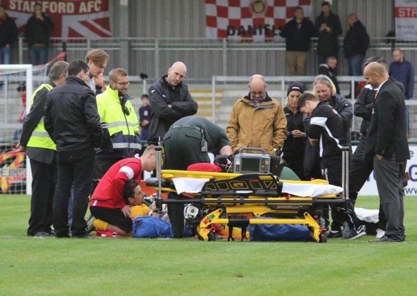 Basford United captain Jake Sheridan is treated on the pitch at the Zeeco Stadium on Saturday after breaking his tibia and fibula bones in his lower leg in a tackle against Stamford AFC. Photo: Geoff Atton EMN-161110-141041001