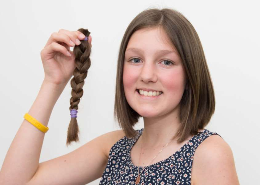 Lucy Rose, 14, pictured with the hair she had cut off for charity