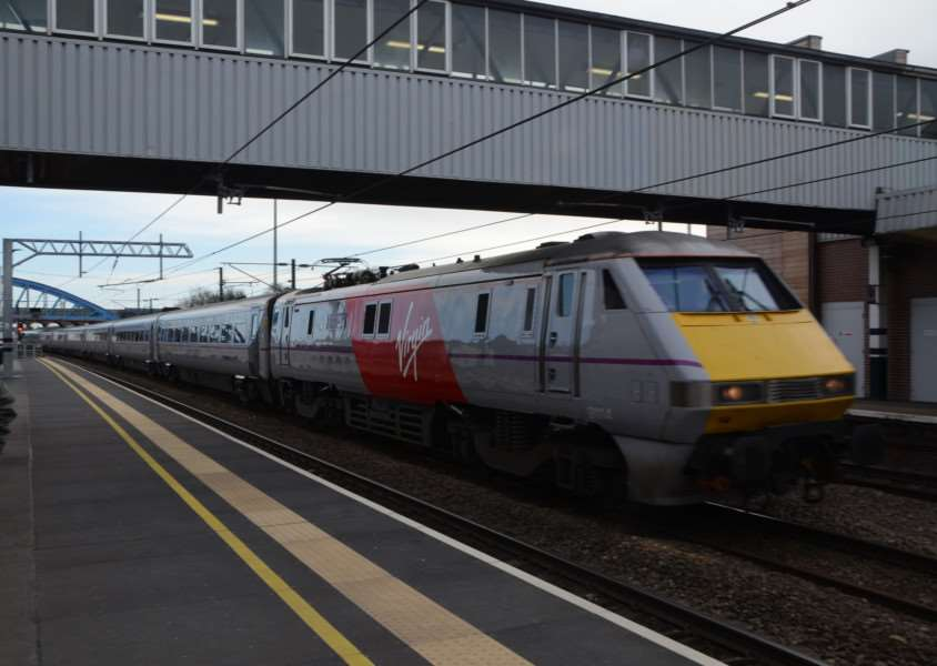 Virgin marked train passing through Peterborough Train Station EMN-150103-190007009