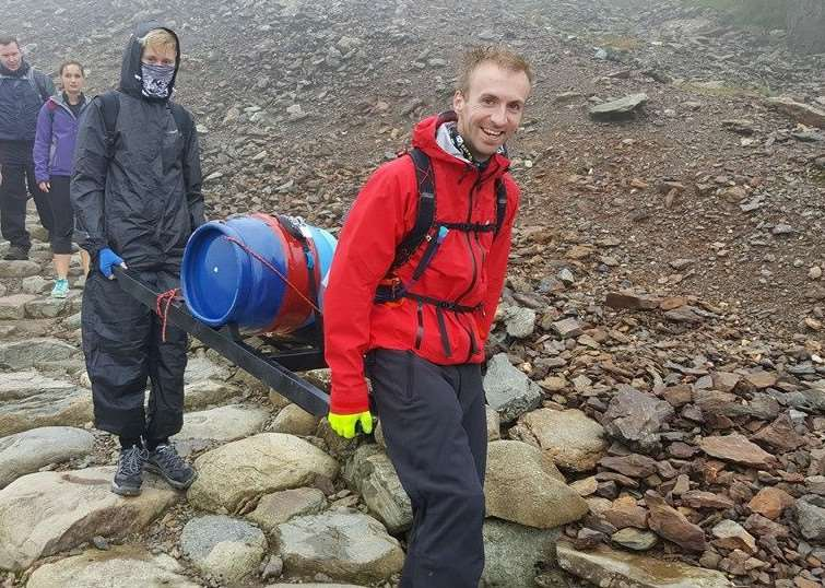 Tom Bellis, right, and Sam Edley carry their barrel of beer on Mount Snowdon