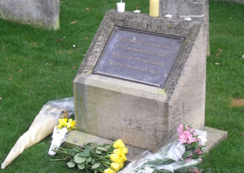 The memorial stone in the grounds, surrounded by flowers laid during the service