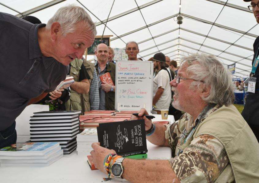 Birdfair 2015 at Rutland water. One of the celebrities at the event Bill Oddie signing book for Anthony Skyrme EMN-150821-174118009