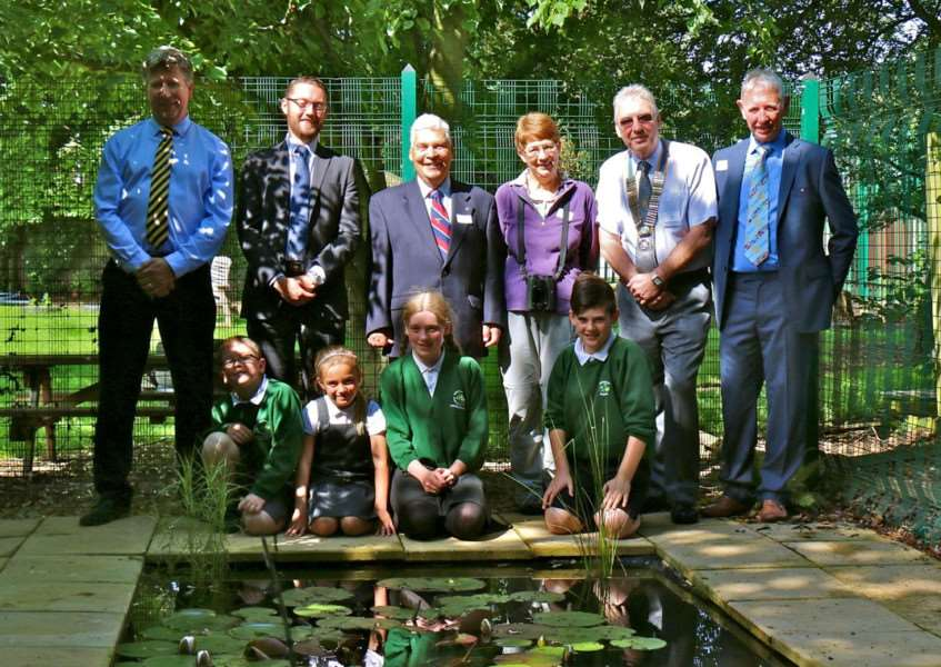 From left: Scott Reeve, outdoor learning co-ordinator, headteacher Andy Fawkes, and Rotarians Tom''Johnson, Sue Titman, Ken Littlemore and Carl''Midgley with some of the pupils at Linchfield Community Primary School's restored pond area EMN-160721-123517001