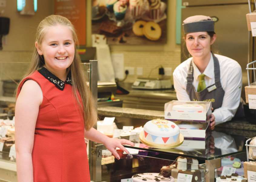 PIC BY GEORGI MABEE/ CATERS NEWS - (PICTURED: CATERS NEWS - (PICTURED: Tilly Chisholm, age nine, pictured at the patisserie section of Waitrose, Stamford, with customer service assistant Abbie Babb. Tilly has won a cake design competition run by Waitrose to celebrate Her Majesty the Queens 90th Birthday.) - EMN-160418-091426001
