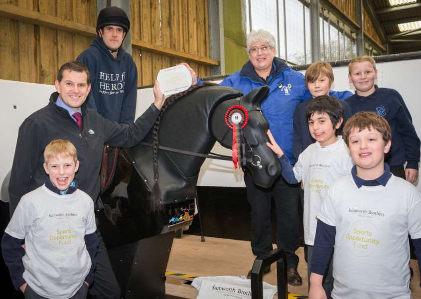 Joseph Platt rides Jet, the new mechanical horse at The Mount Group riding school for the disabled at Somerby, with Samworth Brothers Sports Opportunity Fund trustee Tim Barker (left), Mount Group trustee Pat Bishop and children from Knossington Grange School and Oakham CE Primary Schooll EMN-160825-135339002