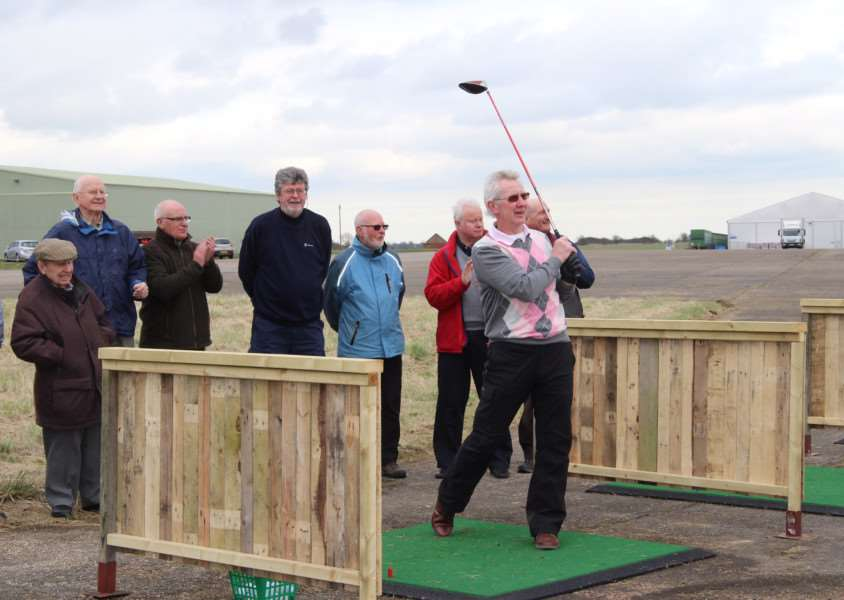 North Luffenham club resident Malcolm Hird opening the new driving range by taking the first drive watched by several club members. EMN-160322-103939001