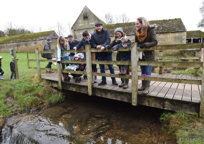 Visitors on the mill bridge enjoy a game of Pooh sticks