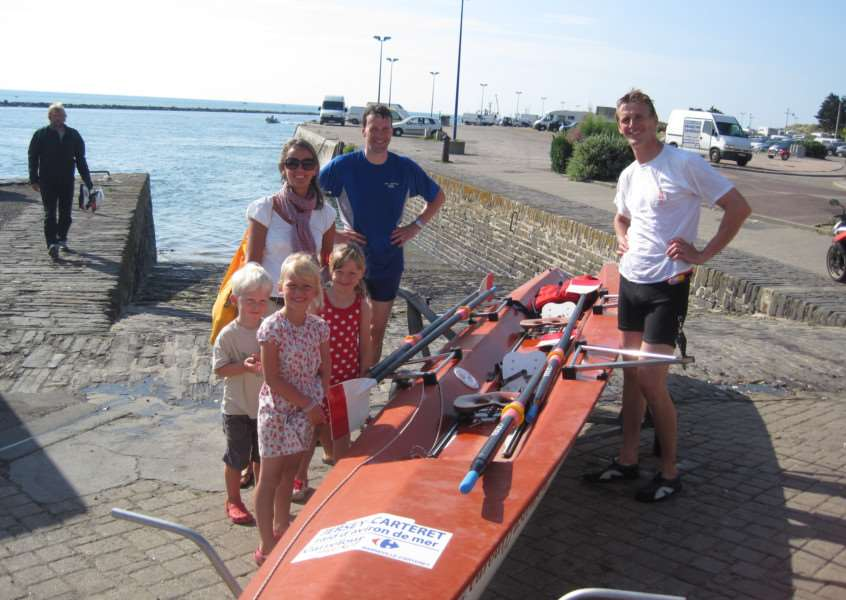 Consultant colorectal surgeon at Peterborough City Hospital Robert Dennis, from Helpston, left will be testing his strength and endurance in a rowing challenge from Jersey to France on July 25. He is pictured with his brother Simon and family. EMN-150619-111932001