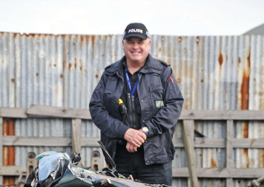Lincolnshire Police rural and wildlife officer PC Nick Willey next to a vehicle crushed after it was seized by police because of its involvement in hare coursing. Photo by Tim Wilson.