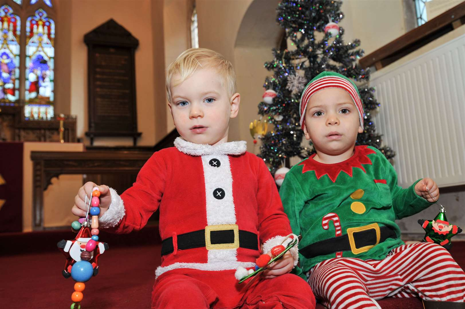Albie and Noah pose in front of the Christmas Tree at Baston Church