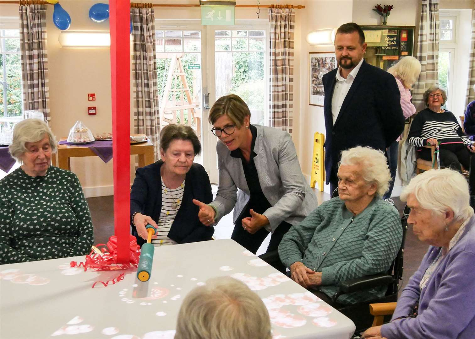 Rutland Care Village residents try out their new magic table watched by former Rutland Lions president Julie Rolland and care home manager Piotr Batory