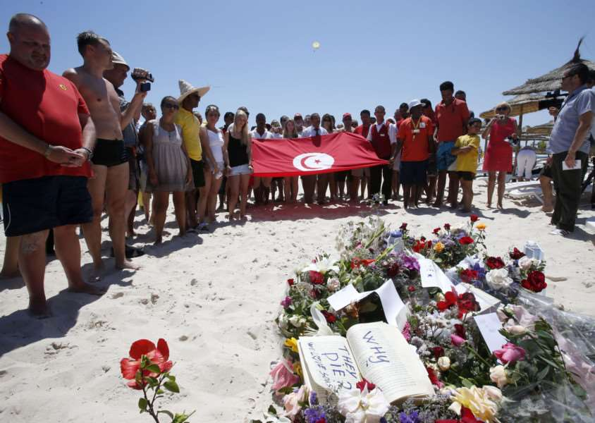 People, some displaying a Tunisian flag, stand in silence next to flowers during a gathering at the scene of the attack in Sousse, Tunisia, Sunday, June 28, 2015. The Friday attack on tourists at a beach is expected to be a huge blow to Tunisia's tourism sector, which made up nearly 15 percent of the country's gross domestic product in 2014. (AP Photo/Abdeljalil Bounhar) EMN-150629-180457001